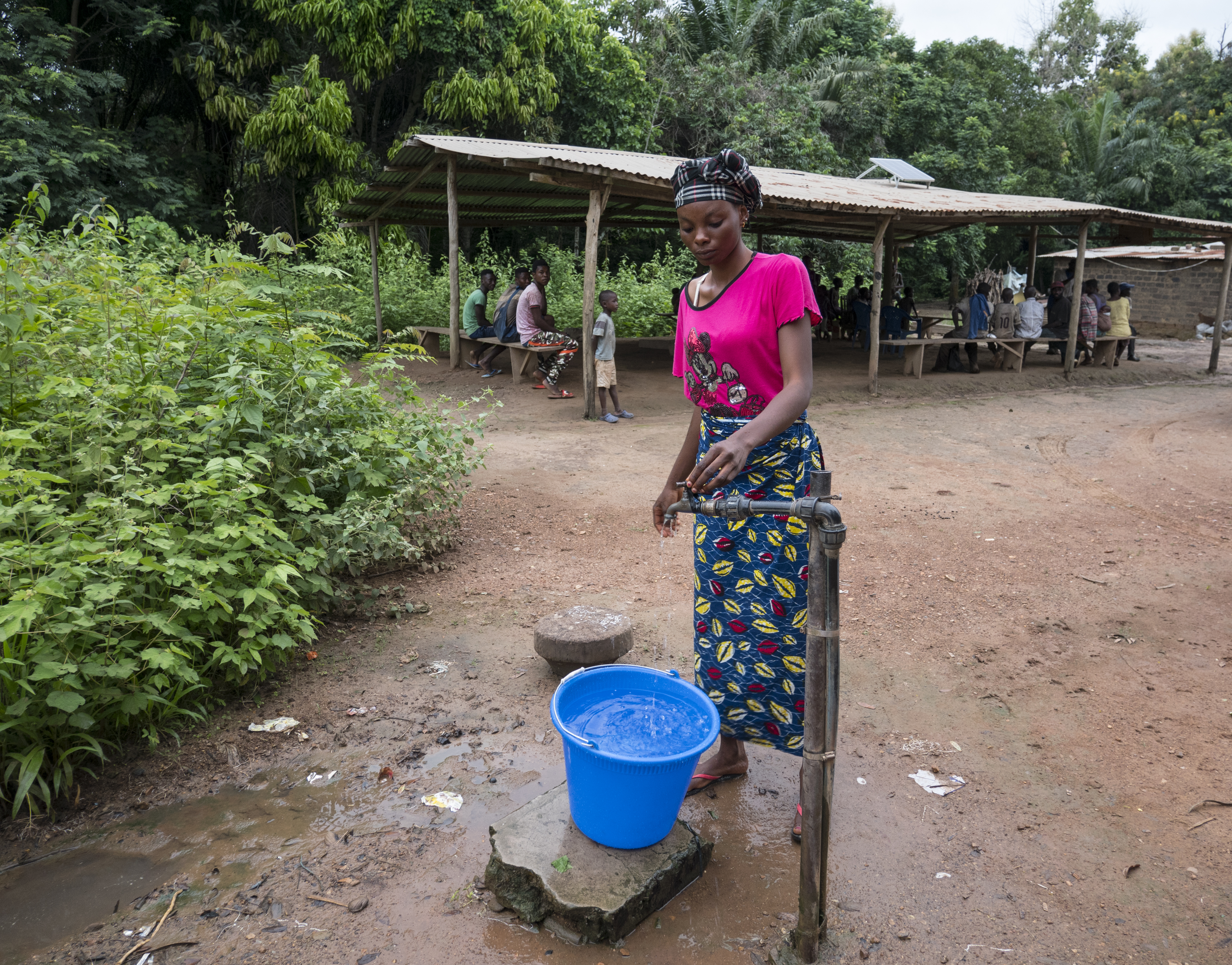 A woman uses the water pump given to the residents of Malolo 2 by Todi River Farms. (Photo by Molly Bergen/WCS, WWF, WRI)