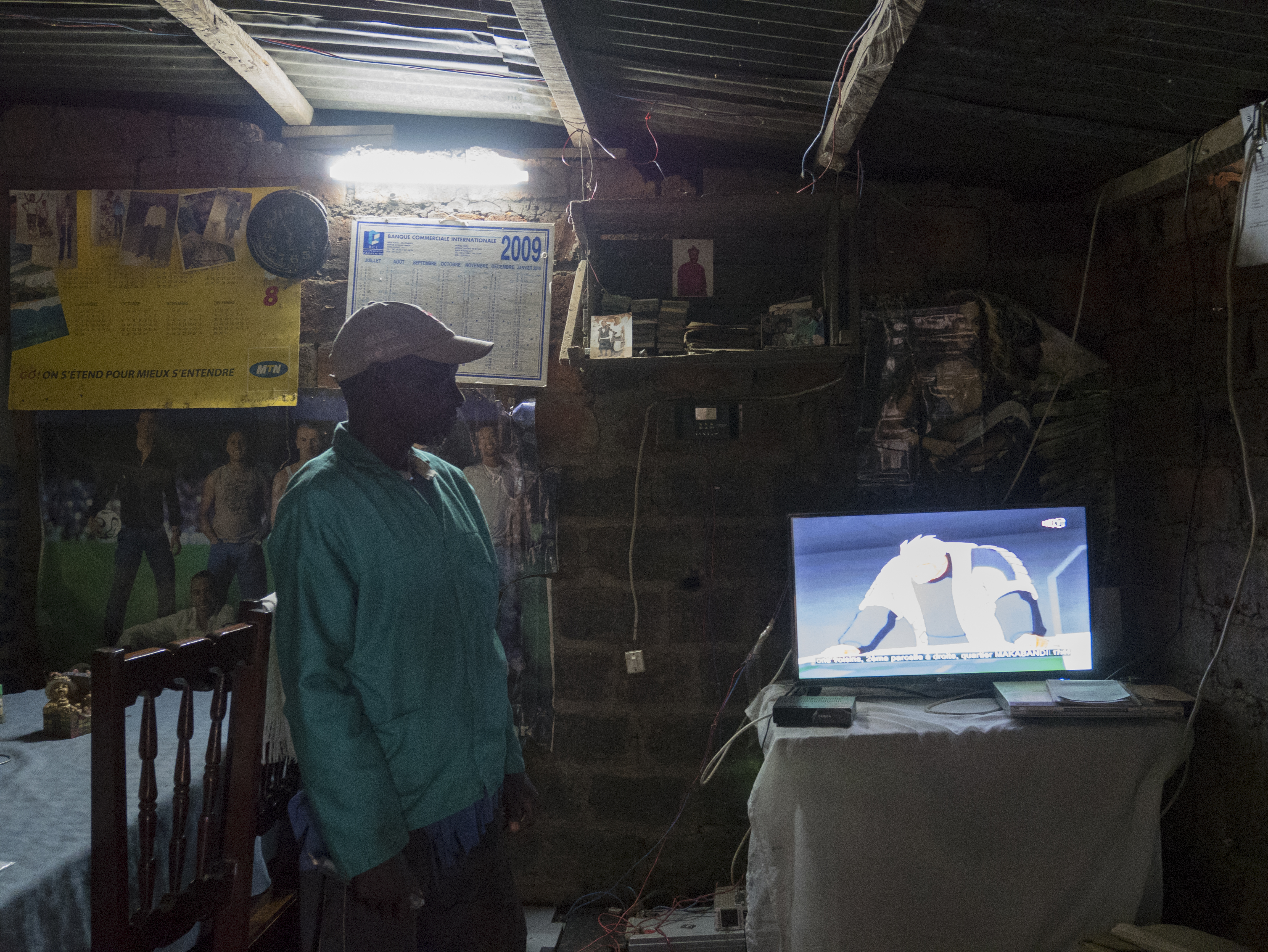 The solar panels in Malolo 2 provide enough electricity to power lightbulbs at night or charge a cell phone. In the case of village chief Jacques Moyo, it also powers his television. (Photo by Molly Bergen/WCS, WWF, WRI)