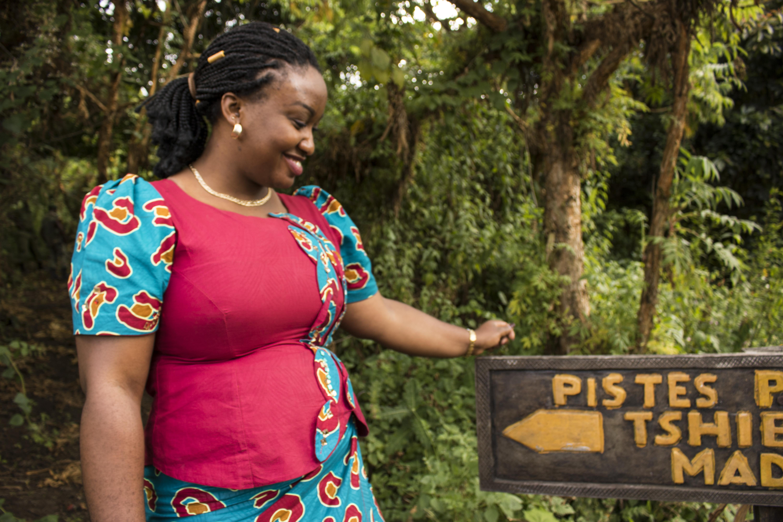 Gloria Mwenge Bitomwa, who leads Kahuzi-Biega's tourism program, at the entrance to a newly restored birding trail near the park's tourist bungalows.(Photo by Molly Bergen/WCS, WWF, WRI)