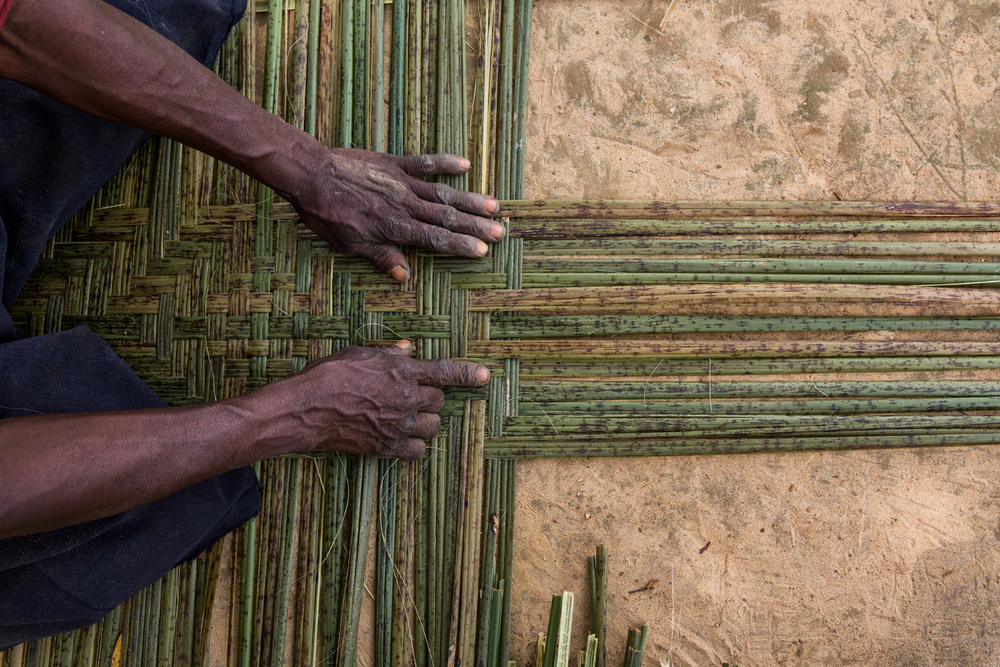 A woman weaves a mat in Mpelu, DRC. Forest products have long been used for everything from building houses to storing food; in modern times they can provide a cheaper and more eco-friendly alternative to plastic. (© Karine Aigner / WWF-US)